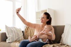 有在家采取selfie的男婴的愉快的母亲 库存图片
