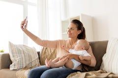 有在家采取selfie的男婴的愉快的母亲 图库摄影