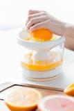 有在家紧压橙汁的剥削者的妇女 图库摄影