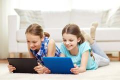 有在家说谎在地板上的片剂个人计算机的愉快的女孩 免版税库存图片