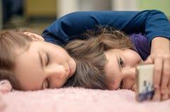 有在家说谎在床和playin上的智能手机的两个小女孩 免版税图库摄影