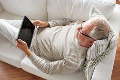 有在家说谎在沙发的片剂个人计算机的老人 免版税库存图片