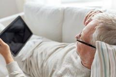 有在家说谎在沙发的片剂个人计算机的老人 免版税库存照片