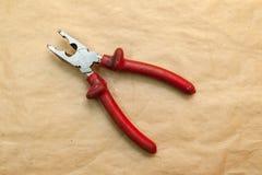 有在工作期间用于的红色橡胶把柄的开放钳子夹紧技巧的零件在工具车间 r 免版税库存图片