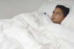 有在床上的温度计的男孩 免版税库存图片