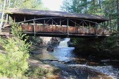 有在底下瀑布的一座被遮盖的桥 库存照片