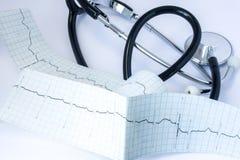 有在心电图附近ECG磁带的黑空气管道管的听诊器与脉冲踪影一条线的位于桌 图库摄影
