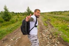 有在手中一台照相机的一个旅游人,与照片的e背包 图库摄影