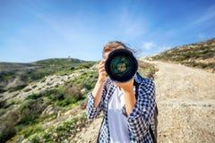 有在手中一台照相机的女孩旅客,反对一个美好的夏天 库存图片