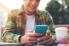 有在手中坐在街道咖啡馆和使用的智能手机的微笑的人信使 免版税库存照片