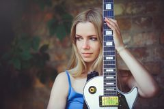 有在手中拿着墙壁背景的一把白色吉他的可爱的谦虚年轻白肤金发的妇女害羞和好奇 免版税库存图片