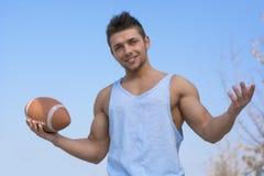 有在手中球的肌肉美国橄榄球运动员,胳膊打开 库存图片