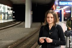 有在手中等待地铁的票的女孩乘客 单独旅行的妇女 图库摄影