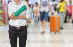 有在手边被熔铸的绿色的受伤的在旅客的妇女和胳膊行动迷离的在机场内部背景中,身体伤害概念 库存照片