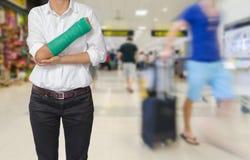 有在手边被熔铸的绿色的受伤的在旅客的妇女和胳膊行动迷离的在机场内部背景中,身体伤害概念 库存图片