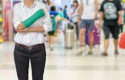 有在手边被熔铸的绿色的受伤的在旅客的妇女和胳膊行动迷离的在机场内部背景中,身体伤害概念 免版税库存照片