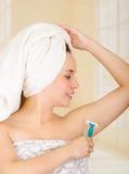 有在拿着蓝色剃刀的阵雨毛巾以后的美丽的新鲜的女孩刮腋窝腋下 库存照片
