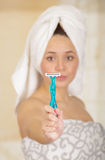 有在拿着蓝色剃刀的阵雨毛巾以后的美丽的新鲜的女孩 免版税库存图片