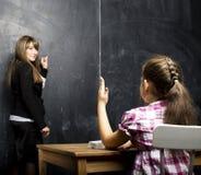 有在教室学习在bla的年轻老师的小逗人喜爱的女孩 免版税库存照片