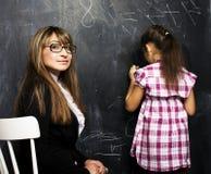 有在教室学习在bla的年轻老师的小逗人喜爱的女孩 免版税库存图片