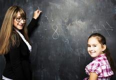 有在教室学习在bla的年轻老师的小逗人喜爱的女孩 库存照片