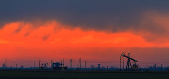 有在日落天空和抽油装置的油田描出的油泵 免版税库存照片