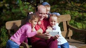 有在智能手机拍摄的孩子的一个人坐长凳 采取selfie的愉快的家庭在公园 家庭 股票视频
