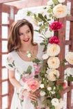 有在有花的夏天礼服穿戴的卷发的美丽的年轻深色的妇女 库存照片
