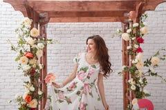 有在有花的夏天礼服穿戴的卷发的美丽的年轻深色的妇女 库存图片
