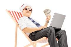 有在椅子供以座位的圣诞老人帽子的老人拿着钞票 免版税库存照片