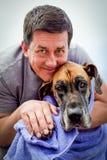 有在毛巾包裹的狗的英俊的人 库存照片