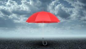有在深灰路面上垂直被安置的黑把柄的一把开放红色伞在风雨如磐的天空背景 库存图片