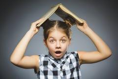 有在灰色背景隔绝的书微笑的想知道的小女孩 免版税库存照片
