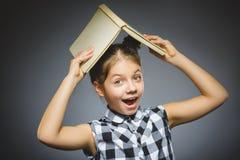 有在灰色背景隔绝的书微笑的英俊的小女孩 免版税库存图片