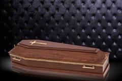 有在灰色豪华背景隔绝的教会十字架的闭合的木棕色棺材 在皇家背景的小箱 图库摄影