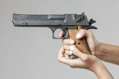 有在灰色隔绝的枪的女性手 免版税图库摄影