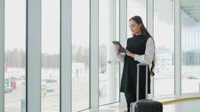 有在片剂计算机上的成功的女实业家在办公室,在窗口企业愉快的微笑的机场附近的妇女 股票录像