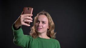 有在电话的一视频通话和修理她的在照相机前面的成人白种人女性特写镜头画象头发 影视素材