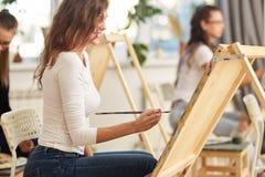 有在白色女衬衫穿戴的棕色卷发的微笑的女孩绘一幅画在画架在画的学校 免版税库存照片