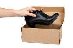 有在白色背景和手的女性黑皮革高跟鞋鞋子隔绝的箱子 库存图片