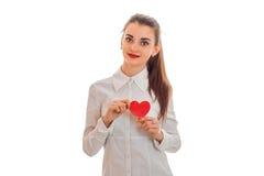 有在白色背景在手摆在隔绝的红色心脏的可爱的年轻深色的妇女 圣徒华伦泰` s天概念 免版税库存图片