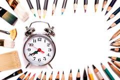 有在白色背景隔绝的缨子的色的铅笔 排行以与闹钟空间的一个卵形框架的形式文本的或 免版税库存照片