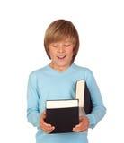 有书的惊奇的青春期前的男孩 免版税库存照片