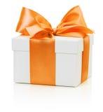 有在白色背景隔绝的橙色弓的白色礼物盒 免版税库存图片
