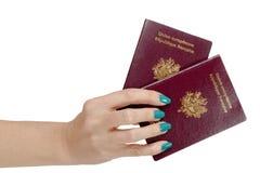 有在白色背景隔绝的,两本法国护照的妇女手 免版税图库摄影