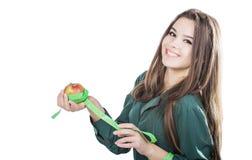 有在白色背景隔绝的黑发的年轻美丽的女孩拿着与卷尺的一个苹果 微笑 免版税图库摄影
