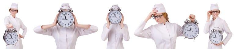 有在白色隔绝的大时钟的可爱的妇女医生 免版税库存照片