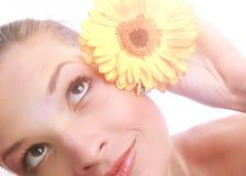 有在白色隔绝的黄色花的年轻美丽的妇女 免版税库存照片
