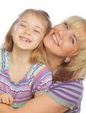 有在白色隔绝的她愉快的妈妈的小女孩 免版税库存照片