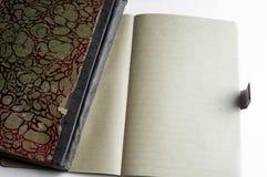 有在白色隔绝的被打开的习字簿的老笔记本的盖子 库存照片